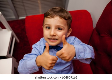 Boy in shirt and tie shows class thumbs