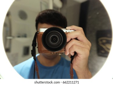 Boy shoot himself through the expanded mirror by camera