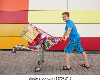 boy with shopping trolley full of purchases in the street