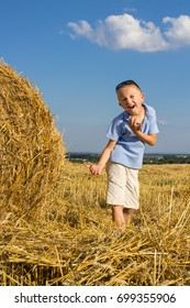 The boy in shorts shows his hands in the field of wheat harvest collected