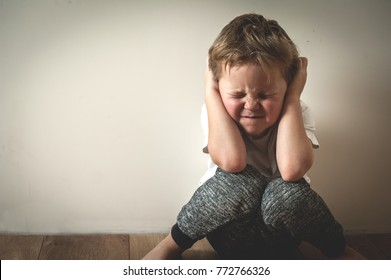 Boy shouts covered his ears with his hands. Stressed child. Domestic Family violence and aggression concept violence. concept for bullying, depression stress or frustration.