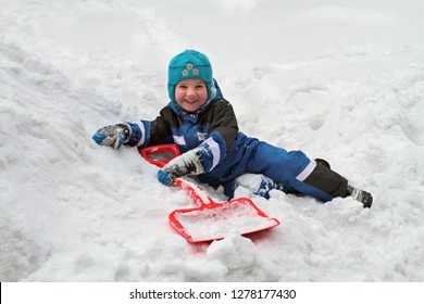 The boy with a shovel laughs lying in the snow