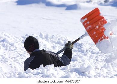 Boy shoveling deep snow