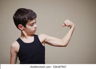 Boy is showing his arm muscles. Portrait of the boy of the European appearance