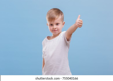 Boy showing thumb on blue background
