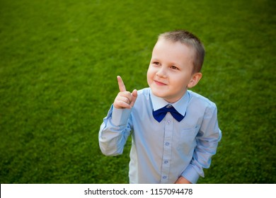 boy shows a finger copy space, green background