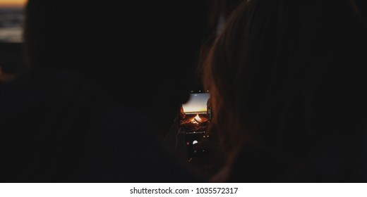 Boy Shows Girl A Picture On His Phone beside campfire on beach
