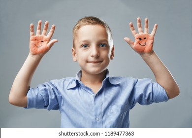 the boy shows hand with drawn emoticons