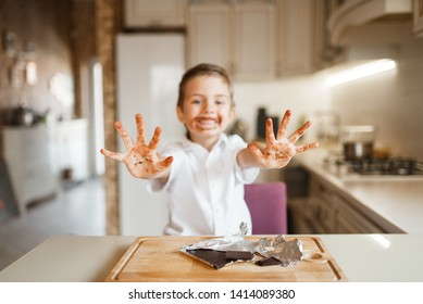 Boy shows hands stained with melted chocolate