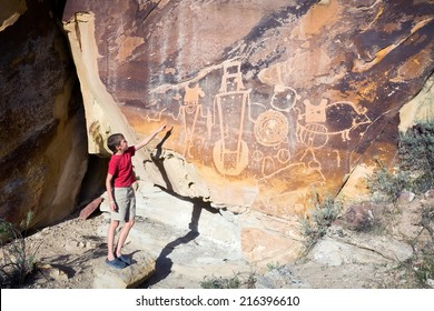A boy shows his hand on the wall with petroglyphs. Dinosaur National Monument (USA. Utah)