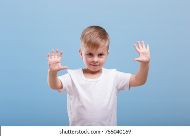 A boy shows his hands on a blue background