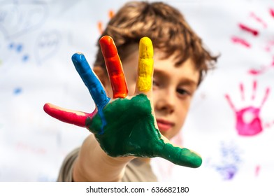 The boy shows the palm painted in different colors