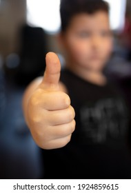 The boy shows a thumb up on his hand. Close-up