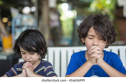 Boy sibling praying together with toned color and selective focus.