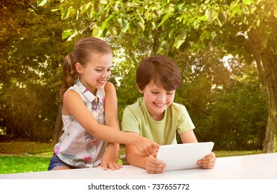 Boy with sister using digital tablet against trees and meadow in the park