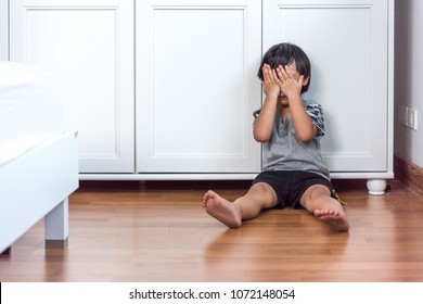 Boy sit in the bedroom crying. Boy hands closed eyes expressing condolences in the white room. Asian boy in black hair sitting in a dirty room and hands dirty in a white room.