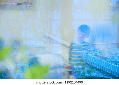 Boy siting home reflection on window longing to walk and play outdoor. Evening snow cold weather at autumn or fall