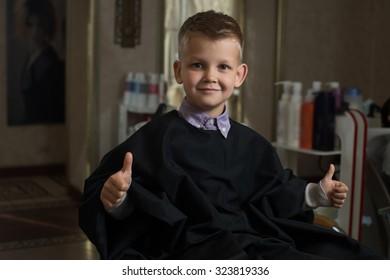Boy sits in barbershop, wearing cape