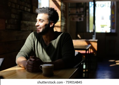 Boy sits in comfortable caf and drinks coffee. Smiling man has dimples, beard, full lips and black hair. Guy dressed in khaki pullover. Concept of comfortable places for wedding tasty coffee.