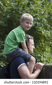 boy sits at the father on shoulders