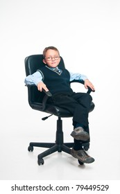 The boy sits in a management armchair on a white background