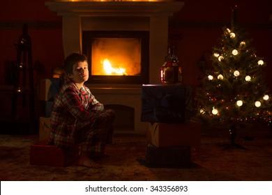 Boy sits near fireplace
