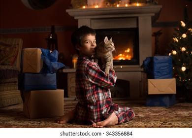 Boy sits near fireplace with a cat