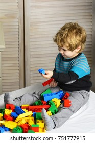 Boy sits on bed and plays with on wooden wall background. Kid builds of plastic blocks. Nursery game and childhood concept. Toddler with smiling face plays with colorful bricks