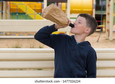 the boy sits on a bench and drinks alcohol from a bottle
