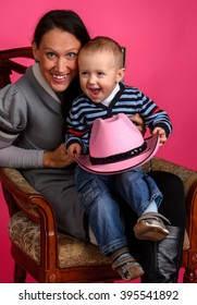 boy sits on a chair next to her mother and holds a cowboy hat