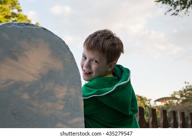 A boy sits on a concrete fence on the street of the resort