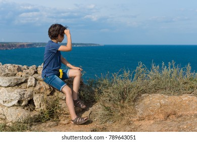 The boy sits on the high seashore and looks out into the distance.