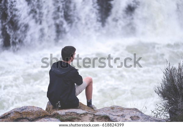 Boy Sits on a ledge of a waterfall