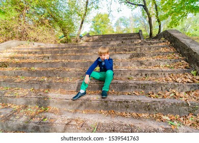 A boy sits on the old steps in the park, wide angle photo bottom view.