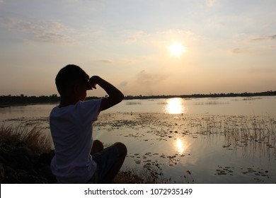 The boy sits on the riverbank and has a flowery grass reflecting sunlight in the evening, a golden background