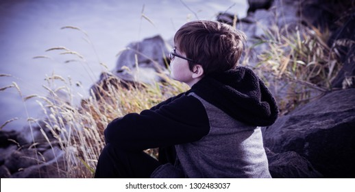 A boy sits on a rocky shore of a lake on a chilly Autumn day, lost in thought as he gazes out onto the water.