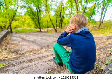 The boy sits on the stairs and looks at the descent, rear view.