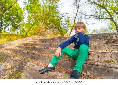 A boy sits on the steps in an old abandoned park, view from below.