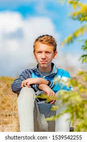 A boy sits on the steps in a park against a cloudy sky.