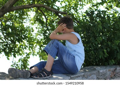 boy sits on stone steps and looks into the distance