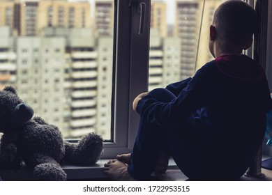 the boy sits on the windowsill and looks out the window sadly