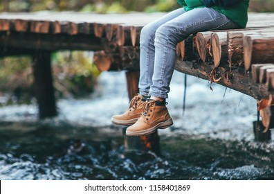Boy sits on the wooden bridge over the river. Close up legs in boots image