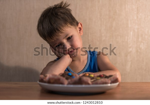 boy sits at the table and looks at the plate with cookies