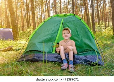 The boy sits in the tourist tent in the green forest.