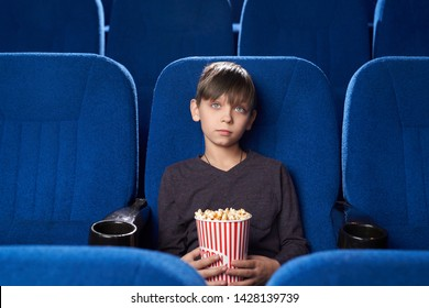 Boy sitting alone in gall of cinema and watching boring film. Male teen with poker face keeping popcorn and looking at screen in movie house. Concept of leisure and entertainment.