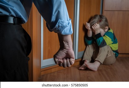 Boy sitting alone leaning on the wall with the father fist. Family violence and aggression concept - furious angry man raised punishment fist over scared or terrified child boy sitting at wall corner