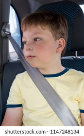 boy sitting in the back seat of car.