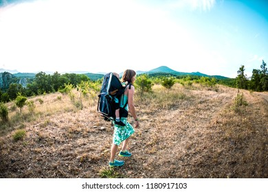 A boy is sitting in a backpack. The kid is traveling with his parents. Climbing with a child. The mother carries the baby. A little traveler. A woman is carrying a backpack with her baby.