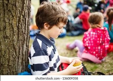 Boy sitting by a tree eating an apple on a school trip