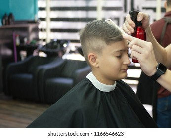 Boy sitting in cair in barbershop while barber combing and wetting his hair